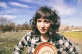 Chica joven con camisa de cuadros y sombrero de paja en un precioso paisaje rural