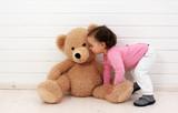 Ein Kleinkind spielt mit seinem Teddybären - 134886626