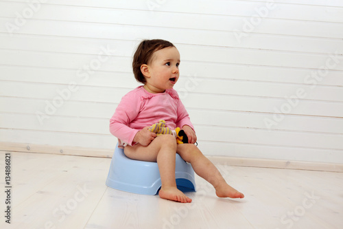 Leinwanddruck Bild Ein Kleinkind sitzt auf einem Töpfchen