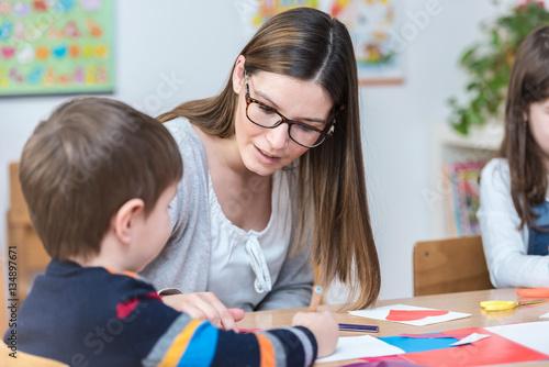 Fototapeta Kindergarten Teacher Supports Child on Class