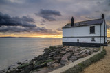 Landscape image of derelict abandoned fishing house on England S