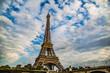 Eiffel Tower set against a cloudy blue sky in Paris, France