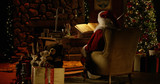 Fototapety Santa Claus works at his desk, surrounded by Christmas decorations