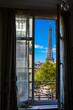 The Eiffel Tower framed through an open window in Paris, France