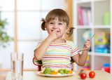 Funny little girl eating healthy food in kindergarten