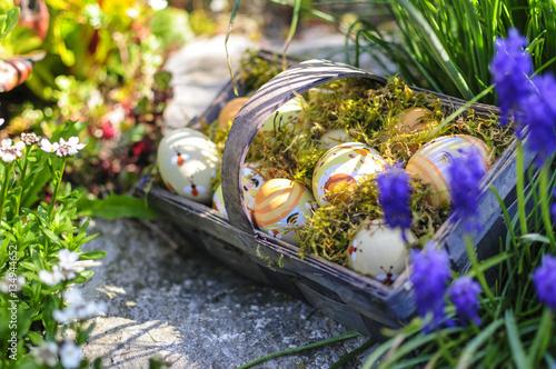Korb mit Ostereiern im blühenden Garten