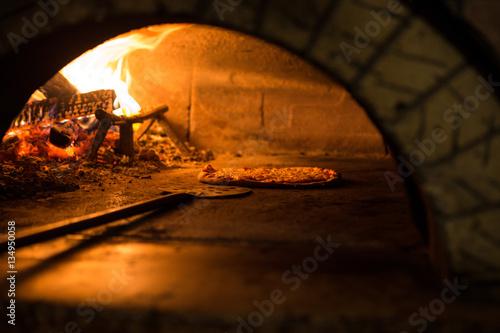 Foto op Plexiglas Pizzeria Pizza cucinata in forno tradizionale a legna