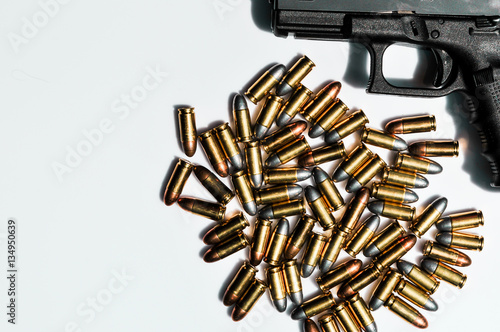 Poster close up of 9 mm. bullets with hand gun on white background