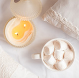 White cup of hot cocoa with marshmallows on white wooden backgro