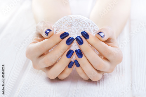 Fotobehang Manicure blue manicure with a white ball of yarn