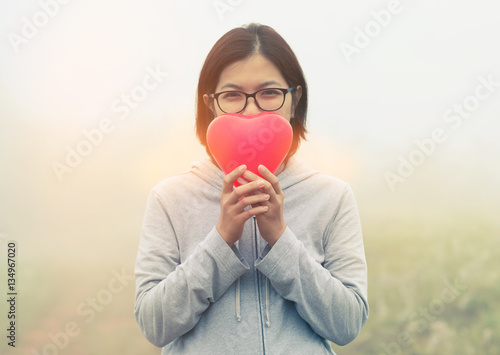 Poster Asian woman holding red heart