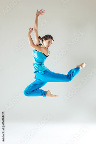 Young beautiful slim girl in blue dancing on a white studio background