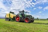 Ernte - Traktor mit Rundballenpresse im Einsatz für Grasssilage - 134988225