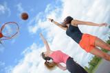 Women playing basketball outdoors