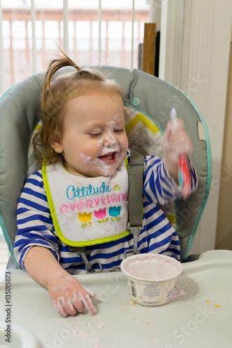 Adorable little girl having fun and making a mess with her yogurt Poster