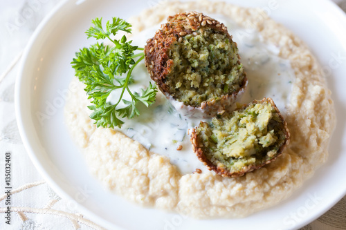 A piece of sliced open pan-frend falafel with tzatziki and sesame seeds