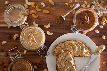 Jars of almond, cashew, and peanut butters sitting in sequence with their respective nuts lying around them