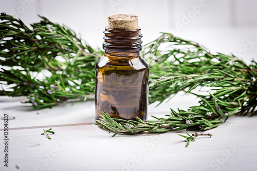 Rosemary essential oil on a  bottle with  fresh rosemary on wooden background, selective focus Poster