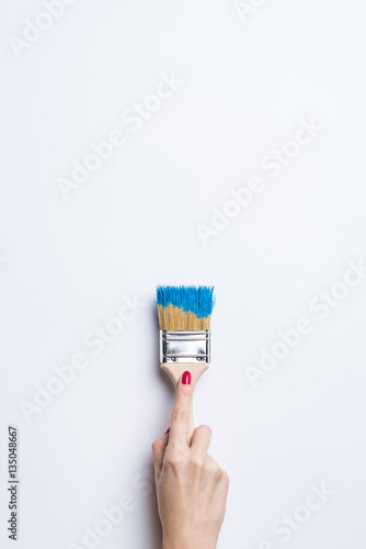 Woman painting empty white wall