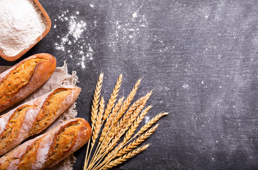 bread with wheat ears and bowl of flour