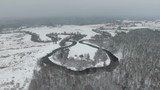 Aero view of winter river and forest. Video.