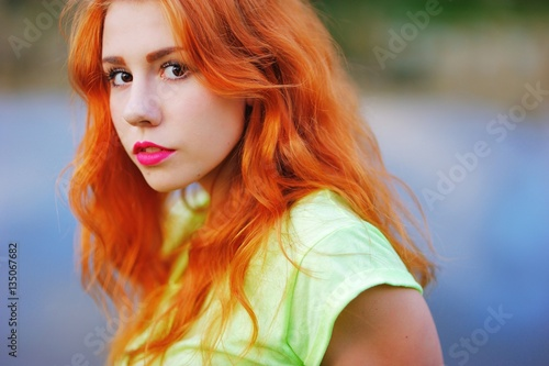 Poster Beautiful young girl with fiery red hair and brown eyes at the lake, close-up