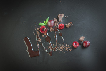 pieces of milk chocolate and cherries on dark background