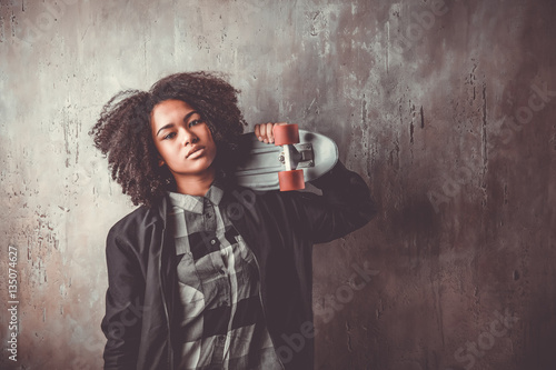 African teenager girl with skateboard in front of a concrete wall