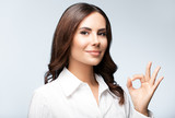 smiling young cheerful businesswoman, showing okay hand sign ges