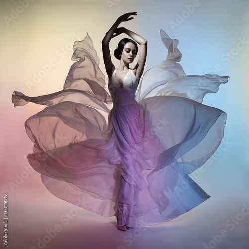Beautiful elegant woman in blowing dress