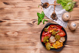 Iron cast pan with grilled vegetables on wooden background