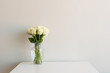 Cream roses in glass vase on white table against neutral wall