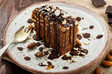 Tasty piece of chocolate Spartak cake on a rustic plate. Traditional delicious dessert on a table.