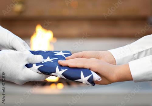 Poster Hands holding folded American flag on Eternal flame background