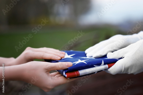 Hands holding folded American flag on blurred background Poster