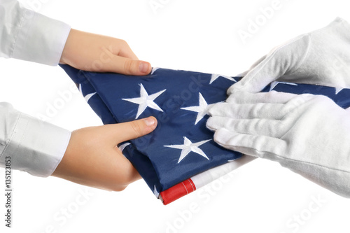 Poster Hands holding folded American flag on white background