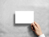 Hand holding blank white postcard flyer mockup. 6 x 4 leaflet mock up presentation. Postal holder. Man show clear post card paper. Sheet template. Invitation booklet reading first person view