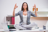 Young businesswoman is meditating in her office.
