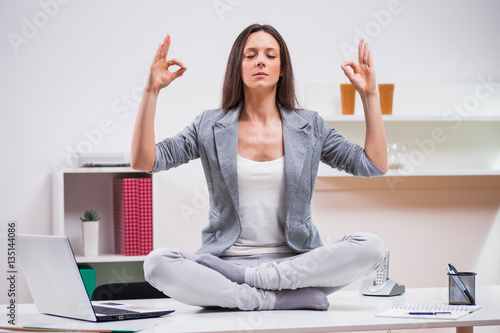 Fototapeta Young businesswoman is meditating in her office.