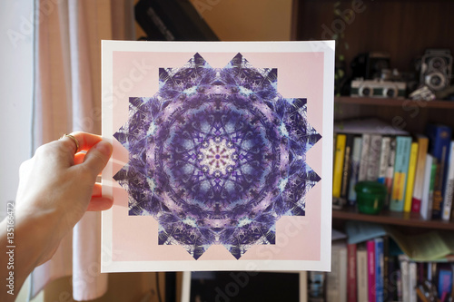 Hand holding abstract mandala picture inside home interior