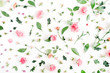 Floral pattern made of pink and beige roses, green leaves, branches on white background. Flat lay, top view. Valentine's background