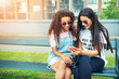 Young women using phone while seated on bench