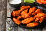Homemade spicy Buffalo chicken wings served with blue cheese dip celery sticks and baby carrots on rustic wooden background - 135197269