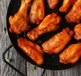 Homemade spicy Buffalo chicken wings served with blue cheese dip celery sticks and baby carrots on rustic wooden background