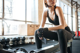 Sportswoman sitting and working out in gym