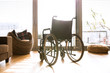 Empty wheelchair in living room next to the couch