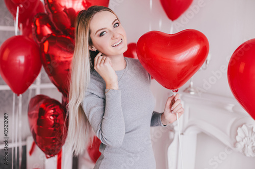 Poster Beautiful young woman posing with red heart balloons in a white room