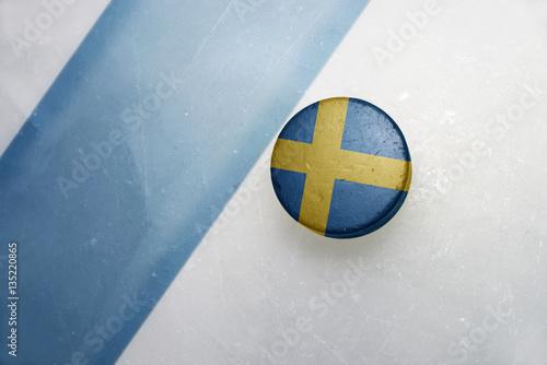 Staande foto Stockholm old hockey puck with the national flag of sweden.