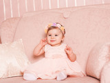 Smiling baby girl 1 year old wearing trendy pink dress and floral hairband sitting on sofa in room.