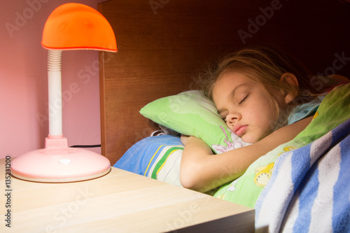 Seven-year girl asleep in bed, reading lamp is included on the next table